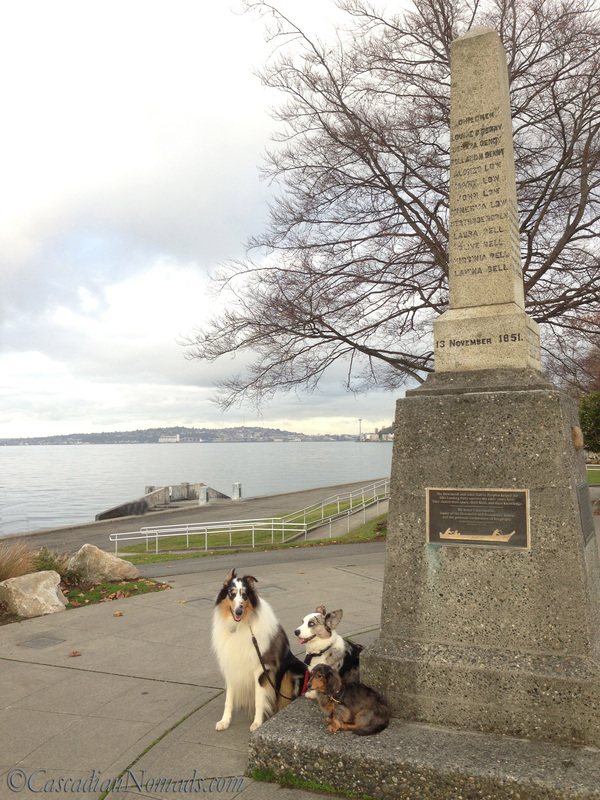 A Remarkable Seattle Site's Historic Monument Sounds Dull But There Are Dogs: collie, dachshund and corgi at the Denny Landing Monument with the Seattle Space Needle in view